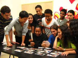 Volunteer with a group of students choose pictures in a teaching project