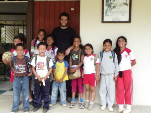 Volunteer in Ecuador with a dozen of children in front of the school