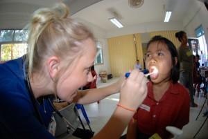 Voluntária examina a boca de uma criança num programa dentário