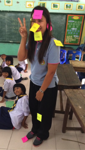 Voluneer smiles to the camera with papers sticked to her face and body in a Teach English Abroad project