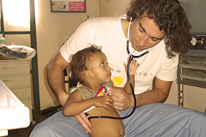 Volunteer listens to the heart of a child in a Medical Health Promotion project