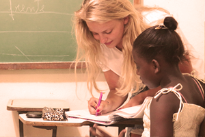 Blond volunteer teach English to young girl