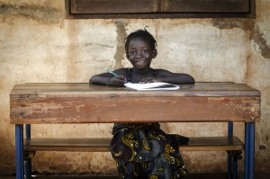 Volunteer in Tanzania teaching in a School: Proud African Schoolgirl Sitting In Her Desk Smiling