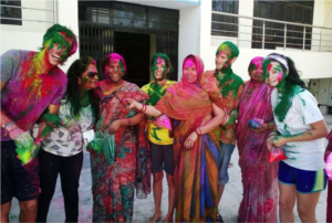 Volunteers all painted with colors smiling together with some locals in traditional dresses