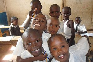 Many children smiling in classroom of a Volunteer in Kenya teaching program