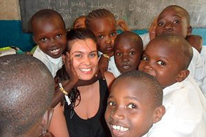 Volunteer with children smiling in a teaching project in Kenya