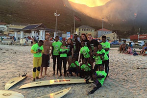 Volunteers and children on the beach in the South African surf school