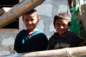 3 children smiling in a child development volunteer program in Nepal