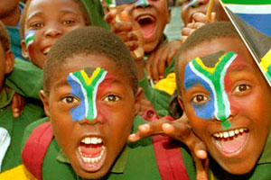 Volunteer in South Africa - kids painted with the flag colors and smiling