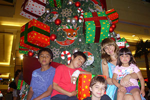 Volunteer in Argentina with 3 children in front a Christmas tree in the Community development project in Argentina