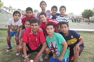10 children with a ball pose to the camera in our program sports volunteer in Argentina