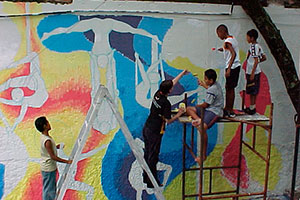 Volunteer painting a big mural with children in our Arts project in Brazil