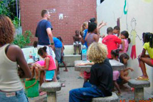 Volunteers in Brazil with many children painting a public space inside a favela