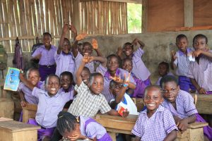 Approximately 20 children smiling in a classroom of one of our Volunteer in Ghana teaching projects