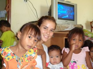 Volunteer in Cambodia with 3 babies smiling in the childcare program