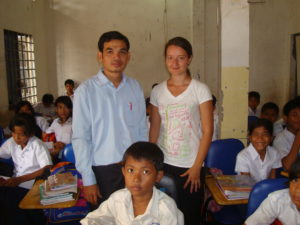 Volunteer in Cambodia together with a teacher inside a classroom in the teaching program