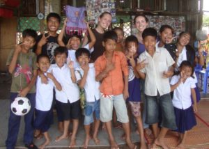 Volunteers in Cambodia with a group of children smiling