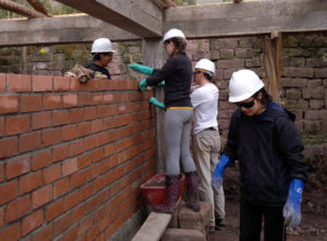 Volunteer building a wall in our construction program