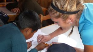 A volunteer in Peru helping a chid to write