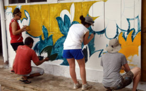 Volunteers painting a mural in our renovation program