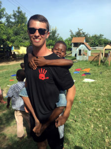 Volunteer in Ghana carrying a boy