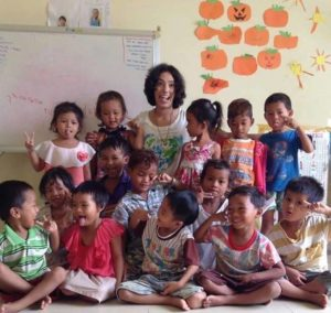 Volunteer with many children smiling in the Caregiving program in Cambodia